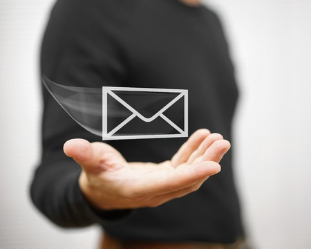 contact: man holds a virtual postal envelope, concept of email, internet and networking