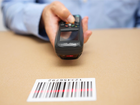 inventario: técnico de almacén inspecciona las cantidades almacenadas con lector de código de barras Foto de archivo