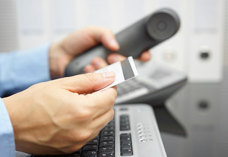 bank office: businessman is holding credit card and calling bank for financial services