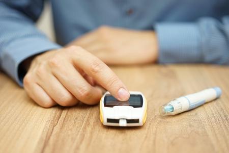 metro medir: nivel de glucosa en las pruebas de hombre con un gluc�metro digital, tratamiento de la diabetes