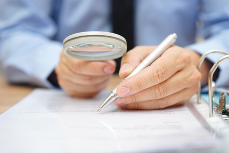businessman is analyzing  through  magnifying glass contract and prices Imagens