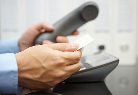 zakenman kijkt op visite kaartje voor informatie om te bellen Stockfoto