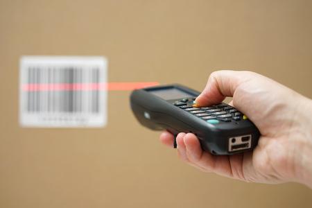 Nahaufnahme der Hand hält Barcode-Scanner und Scan-Code auf Karton
