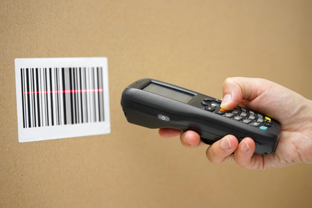 Scanning label on the box with barcode scanner Imagens