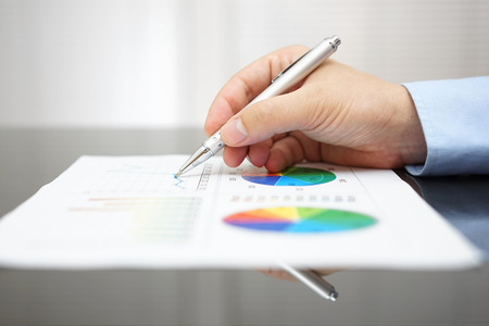 closeup of male hand analyzing business report on black desk