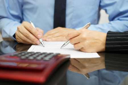 financial agreement: businessman and female coworker are examining financial agreement Stock Photo
