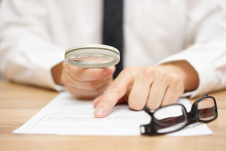 business law: Focused businessman is reading through  magnifying glass document
