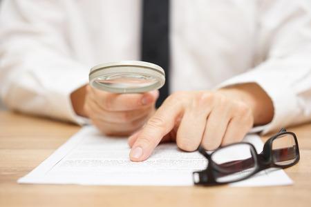 Fokussierte Geschäftsmann durch Vergrößerungsglas Dokumentenlese