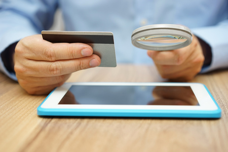 bank transfer: man is using credit card for online payment on tablet  computer with magnifying glass