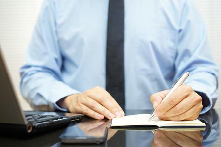 homme d'affaires de prendre des notes sur le bureau à côté de l'ordinateur portable et téléphone mobile