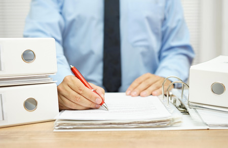 impuestos: Sección media de hombre de negocios trabajando con documentos financieros en el escritorio