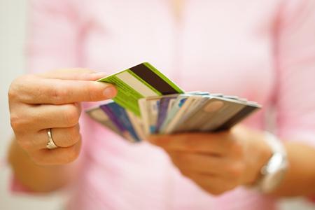 tarjeta de credito: Mujer elegir una tarjeta de crédito de muchos, el concepto de la deuda de tarjetas de crédito,