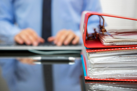 accountant with stack of invoices is inserting data into computer database Foto de archivo