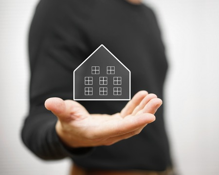 man holding virtual house. Property and real estate concept Standard-Bild