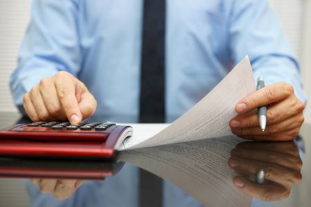 audit: businessman reading  document with numbers and calculating
