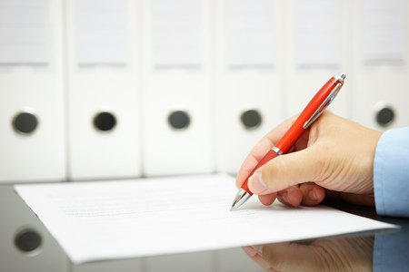 businessman signing documents: closeup of businessman hand writing on document on  office desk