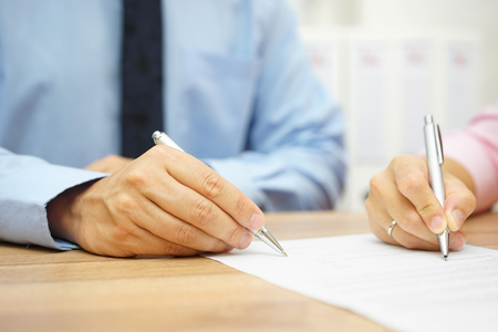 man in office: Businessman and woman hand signing agreement in office