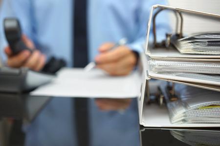 documentos: hombre de negocios en el desenfoque est� trabajando en el escritorio de oficina con el tel�fono en las manos y en el documento delante si �l, se centran en las carpetas