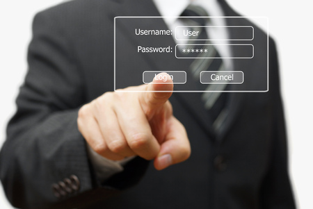 login icon: businessman pressing authentication button on login display Stock Photo