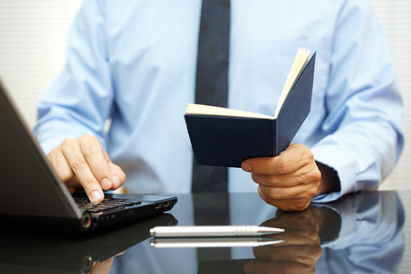 bussinessman is reading informations from notebook and typing on laptop keyboard Stock Photo