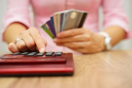 tarjeta de credito: Mujer calcular la cantidad de coste o gasto tienen con tarjetas de crédito