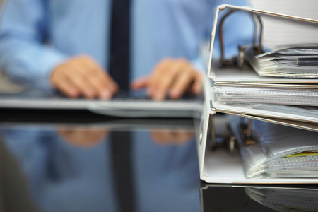 auditoría: empresario borrosa está escribiendo en el teclado de ordenador con Documenation en foco Foto de archivo