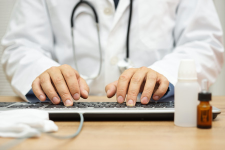 hand job: Doctor is typing diagnose on computer keyboard