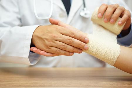 accidente laboral: primer plano de m�dico var�n vendaje mano femenina Foto de archivo