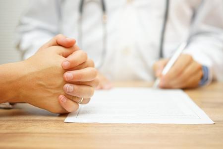 Hände von Concerned Women für einen medizinischen Bericht von einem Arzt über die medizinische Zustand geschrieben