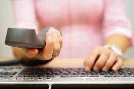 zakelijke vrouw in het kantoor werken op de computer en het aanbieden van de handset