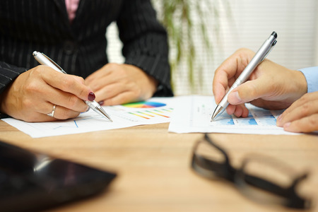 Corporations: businesswoman and businessman are discussing about financial data on meeting Stock Photo