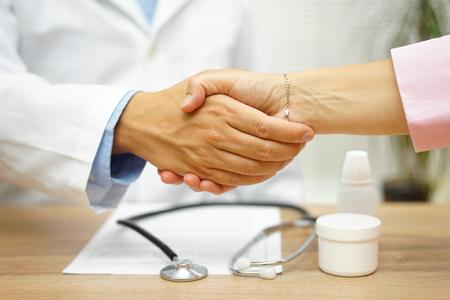 Zufriedene Patienten über eine gute Gesundheit Bericht mit guter Arzt Handshaking