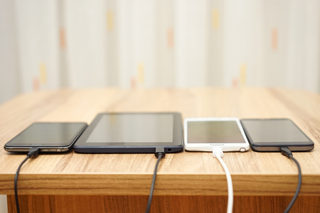 computer tablet and mobile phones charging on home desk