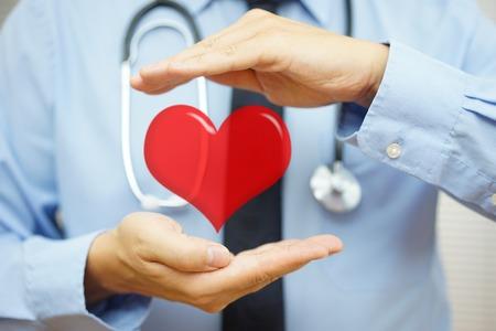 hipertension: médico está protegiendo corazón con las manos. cuidado de la salud y las enfermedades cardiovasculares concepto Foto de archivo