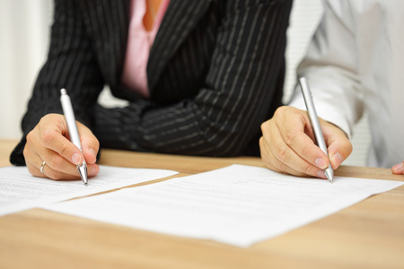 law office: businesswoman and businessman signing contract in the office Stock Photo