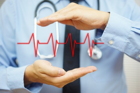 oscillate: cardiologist is protecting with hand heart bit line Stock Photo