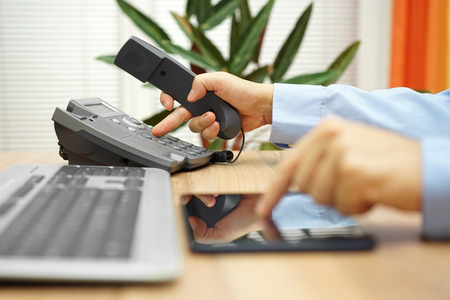 iletişim: Tablet bilgisayar üzerinde çalışan işadamının desteği hizmeti çağırıyor Stok Fotoğraf