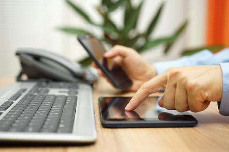Zakenman werkt met tabletcomputer en slimme mobiele telefoon op de werkplek
