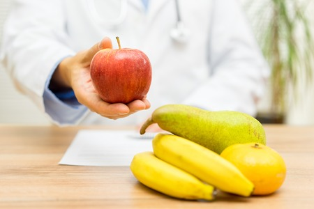 recommending: doctor nutritionist is recommending  eating fruit every day Stock Photo