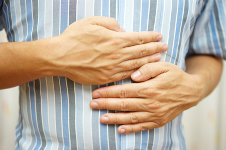 Stomach ache, man placing hands on the stomach, concept of stomach ulcer Stock Photo