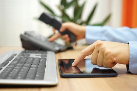 uomo d'affari impegnato con il computer tablet sta componendo il numero di telefono