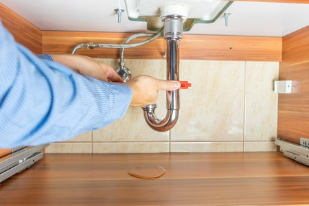 Plumber is repairing a leaky drain in bathroom Stock Photo
