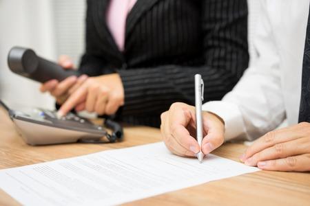 Mensen uit het bedrijfsleven bezig met bellen cliënt of kandidaat en bewerken van documenten interview Stockfoto