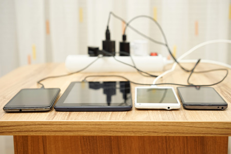 mobile phones and tablet  charging on desk