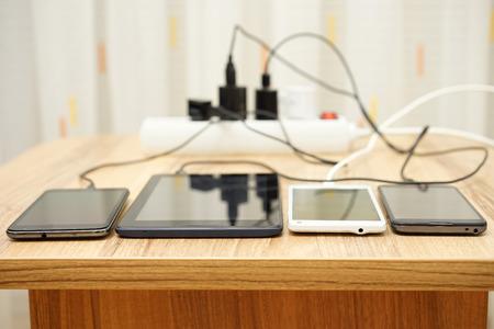 Mobiele telefoons en tabletopladen op bureau
