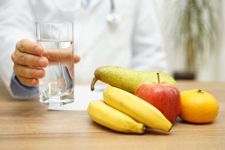 alimentacion sana: El doctor est� ofreciendo agua y fruta despu�s de leer a diagnosticar. concepto de vida sana y el cuidado de la salud