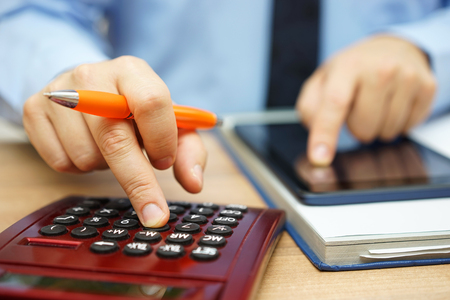 financial analyst  is calculating return on investment with financial papers and on line data Stock Photo