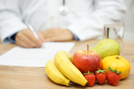 dietology: Nutritionist Doctor writing diet plan, focus on fruit and water