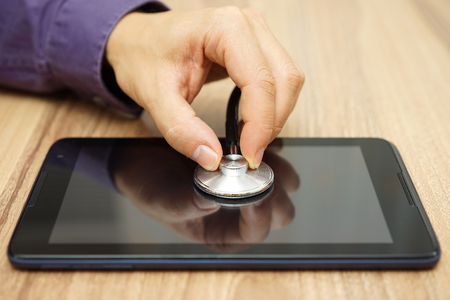 find fault: male  hand  is holding a stethoscope over tablet computer, repair service for tablet and laptop Stock Photo