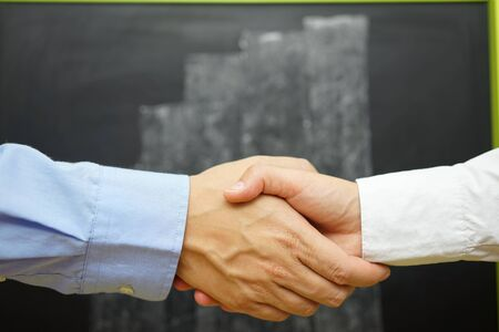 growing partnership: closeup of business handshake with blurred  growth graph on blackboard